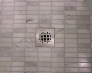 Shower floor tile is 1x2 marble tiles that look like minis of the floor tile.